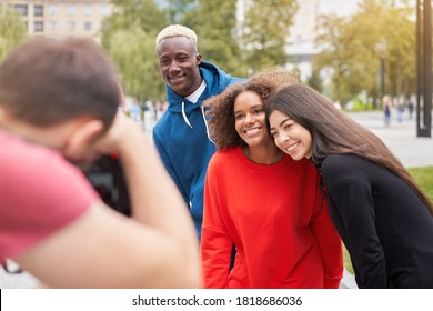 Multi ethnic friends outdoor Student one man two woman posing for photographer