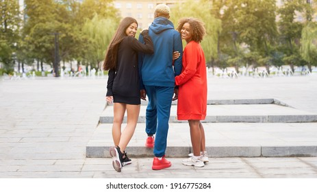 Multi ethnic friends outdoor. Two woman in love with one guy Diverse group people Afro american asian spending time together Multiracial male female student walking park outdoors