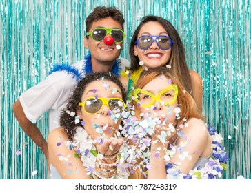 Multi ethnic group of Brazilian friends. Costumed revelers are happy and celebrating the Carnival with much celebration. Beautiful woman blows the confetti of the palm of the hand.