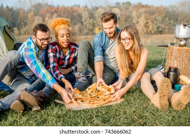 Multi ethnic group of firends dressed casually having fun eating pizza during the outdoor recreation