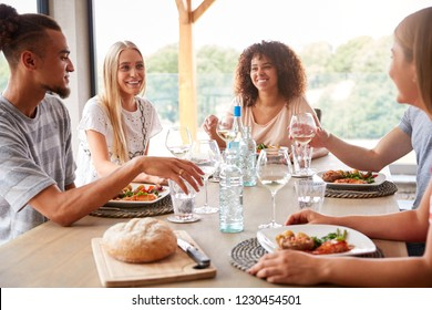 Multi ethnic group of five young adult friends eating, drinking,  talking and smiling during a dinner party