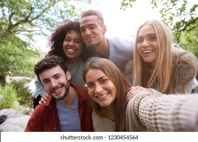 Multi ethnic group of five young adult friends pose to camera while taking a selfie during a break in a hike