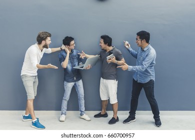 Multi ethnic group of four men fighting while using laptop computer, digital tablet together with copy space on blue wall. Lifestyle information technology gadget education or social network concept.