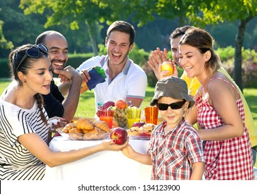 Multi ethnic group of friends enjoying a meal together outdoors in the garden with a small boy in sunglasses in the foreground