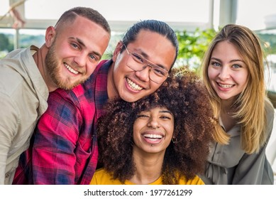 Multi ethnic group of friends taking selfie indoor with a curly woman in foreground.two young women and two men in summer.people taking self portrait.Happy concept of students having fun together