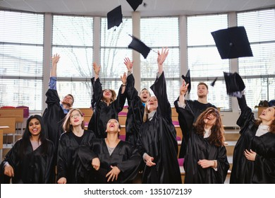 Multi ethnic group of graduated students throwing hats