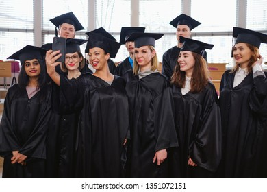 Multi ethnic group of graduated students taking selfie