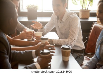 Multi ethnic group of happy friends drinking coffee in paper cups together in cozy cafe, diverse multiracial african and caucasian young people talking sharing table having fun at coffeehouse meeting