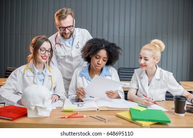 Multi ethnic group of medical students in uniform studying together sitting at the desk with books in the modern classroom
