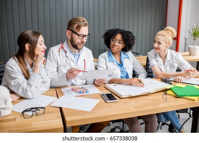Multi ethnic group of medical students in uniform having a discussion sitting together at the desk with different medic stuff in the classroom