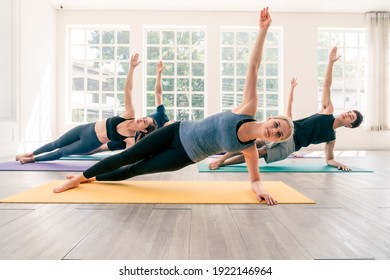 Multi ethnic group of people (Asian, Caucasian) practice yoga together in studio room. Caucasian woman instructor lead side plank pose. Concept of diversity and healthy lifestyles.