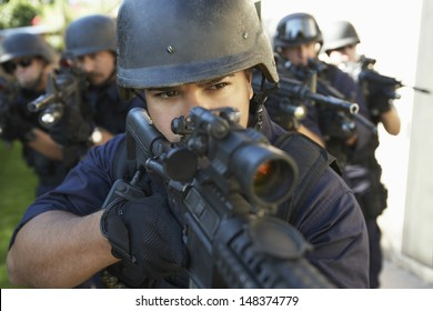 Multi ethnic group of police officers aiming with guns