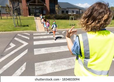 Groupe multiethnique d'écoliers portant des masques faciaux, traversant la rue avec une femme de la police caucasienne disant qu'elle était en sécurité. L'éducation est de retour à la sécurité sanitaire à l'école pendant la pandémie de Coronavirus du 19 novembre.