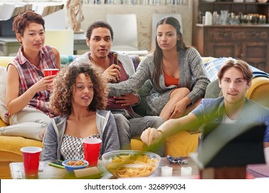 Multi ethnic group of  student friends hanging out at home huddled on couch together excitedly watching football event on TV drinking beer  eating snacks anticipating winning goal