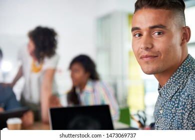 Multi ethnic group of succesful creative business people using a laptop during candid meeting