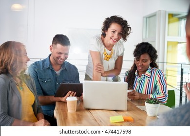 Multi ethnic group of successful creative business people using a laptop during candid meeting