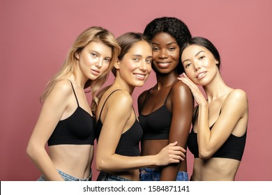 Multi Ethnic Group of Womans with diffrent types of skin standing together and looking on camera. Diverse ethnicity women - Caucasian, African and Asian against pink background