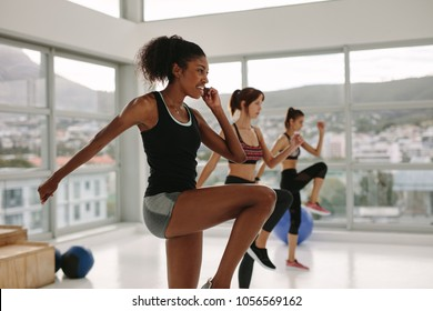 Multi ethnic group of women doing stretching exercises before intensive workout in spacious fitness studio. African female doing exercise with women in background.