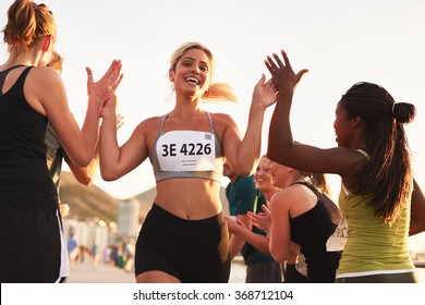 Multi ethnic group of young adults cheering and high fiving a female athlete crossing finish line. Sportswoman giving high five to her team after finishing the race.