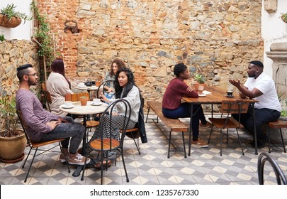 Multi ethnic group of young people enjoying coffee and talking while sitting together at tables in the courtyard of a trendy cafe