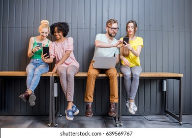 Multi ethnic group of young people dressed in colorful t-shirts chatting with gadgets sitting in a row indoors on the wall background