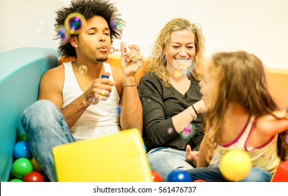 Multi ethnic parents playing with daughter inside ball pit swimming pool - Happy people having fun in children playground indoor - Family and love concept - Focus on woman face - Warm filter