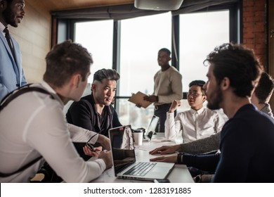 Multi ethnic people entrepreneurs meeting, small business concept. Afro american chief executive of big company presents new marketing strategy to coworkers gathering around a conference table.