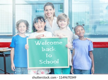 Multi ethnic primary classroom with teacher holding back to school sign chalkboard.