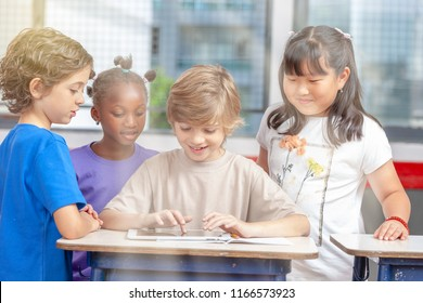 Multi ethnic schoolmates in primary school playing with tablet, sun rays coming from outside.