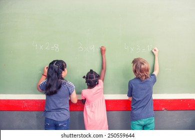 Multi ethnic schoolmates writing math at chalkboard.