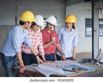Multi ethnic team of engineers and technician meeting  in building site.