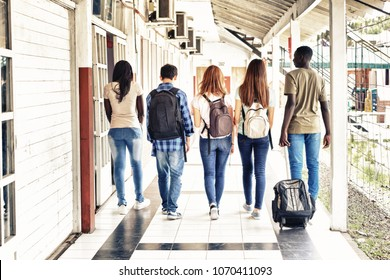 Multi ethnic teenagers friends walking in the school hallway, back view.