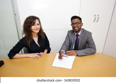 Multi ethnic work colleagues signing paperwork on a table