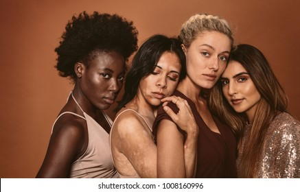 Multi ethnic young women friends with different skin types. Diverse group of females standing together on brown background.