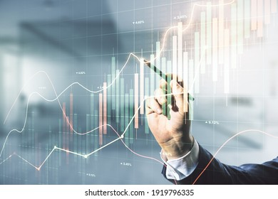 Multi exposure of businessman hand with pen working with virtual creative financial chart hologram on blurred office background, research and analytics concept - Shutterstock ID 1919796335