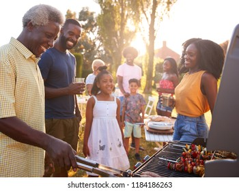 Multi generation black family barbecue, grandad grilling