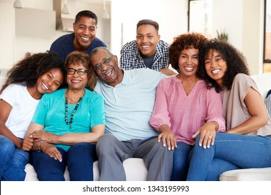 Multi generation black family sitting at home smiling to camera