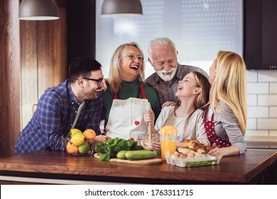 Multi Generation Family Cooking Meal At Home