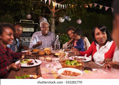 Multi generation family eating dinner in garden, close up