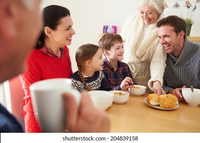 Multi Generation Family Eating Lunch At Kitchen Table