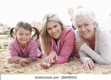 Multi Generation Family Lying On Beach Together