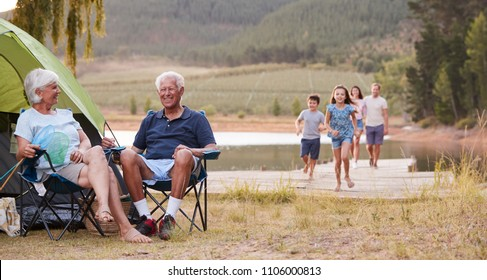 Multi Generation Family On Camping Trip By Lake Together