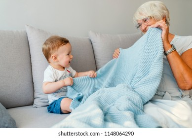 Multi generation family playtime. Senior woman hold little baby cute smiling. Happy grandmother with her grandchild in home. Beautiful grandma and grandson playing together having fun at home