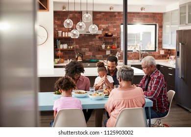 Multi Generation Family Praying Before Meal Around Table At Home