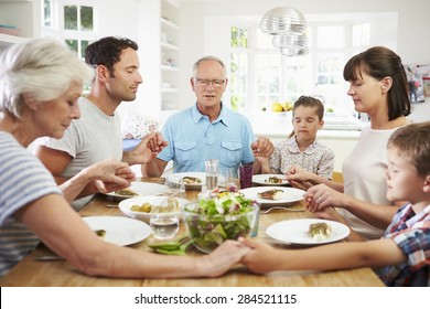 Multi Generation Family Praying Before Meal At Home