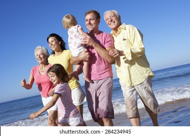 Multi Generation Family Running Along Beach Together