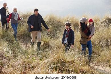 Multi Generation Family In Sand Dunes On Winter Beach
