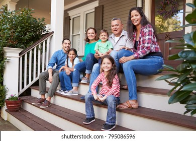 Multi Generation Family Sit On Steps Leading Up To House Porch