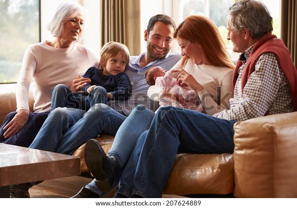 Multi Generation Family Sitting On Sofa With Newborn Baby