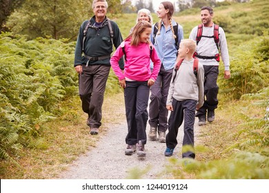 Multi generation family talk while walking in the countryside during a camping holiday, full length